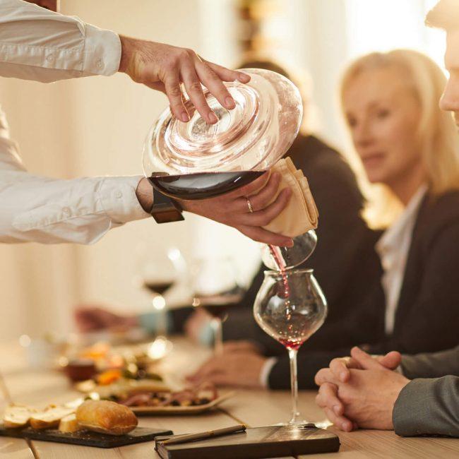 sommelier pouring wine closeup ZKM8XLY